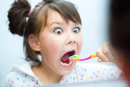 Petite fille se brossant les dents.